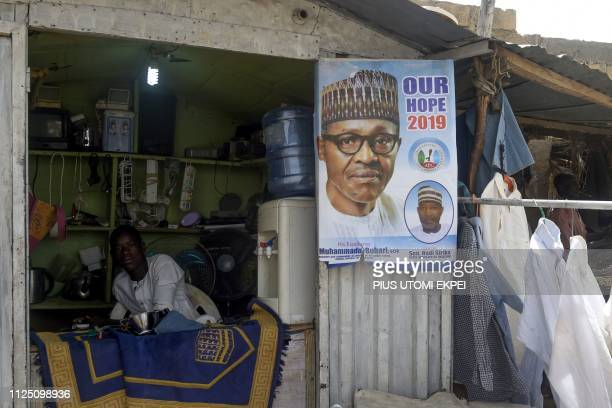 TOPSHOT A tailor on his shop displays a poster bearing a picture of candidate of ruling All Progressives Congress President Mohammadu Buhari in Daura...