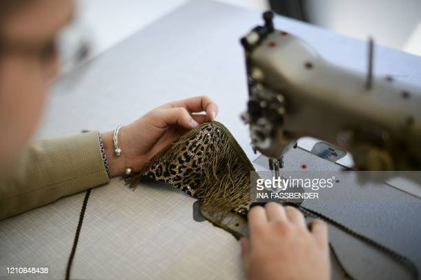 Tailor Pierre Zielinski sews a fashion protective face mask at Wolfgang Schinke's tailoring studio in Krefeld western Germany on April 22 amid the...