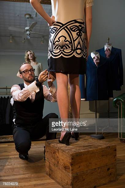 Tailor pinning female model's skirt, model with hand on hip