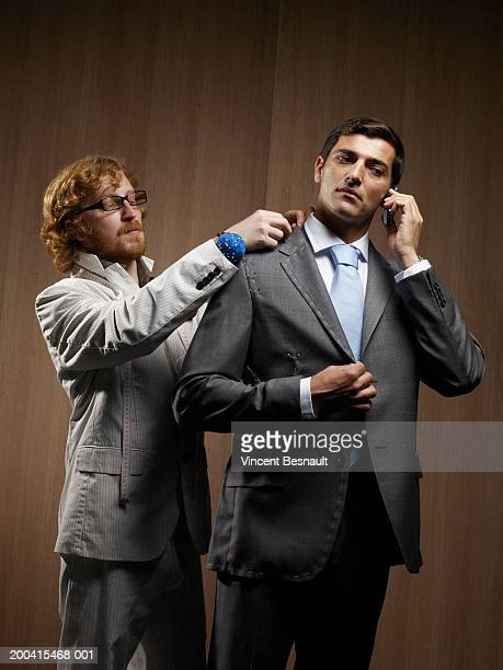 Tailor pinning suit on man using mobile phone, low angle view