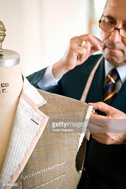 Tailor pins man's coat shoulder