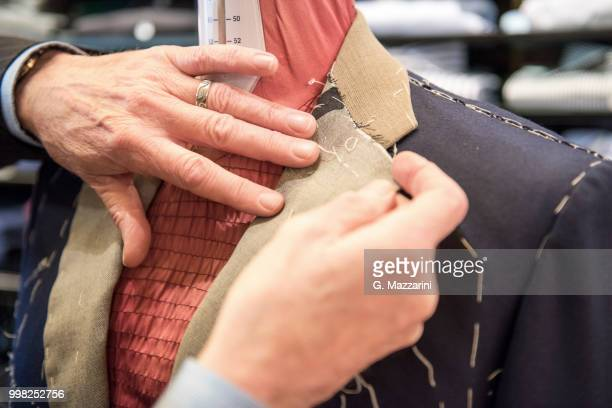 tailor preparing bespoke suit jacket on tailors dummy, close up of hands - customized stock pictures, royalty-free photos & images
