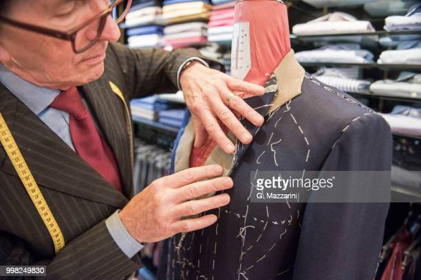 tailor preparing bespoke suit jacket on tailors dummy - custom tailored suit stock pictures, royalty-free photos & images