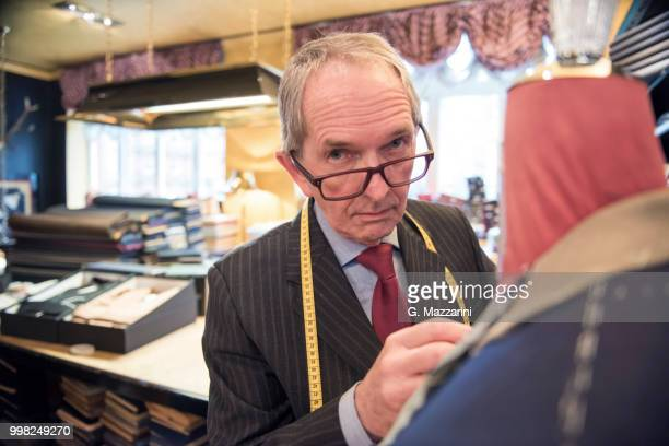 tailor preparing bespoke suit jacket on tailors dummy, portrait - custom tailored suit stock pictures, royalty-free photos & images
