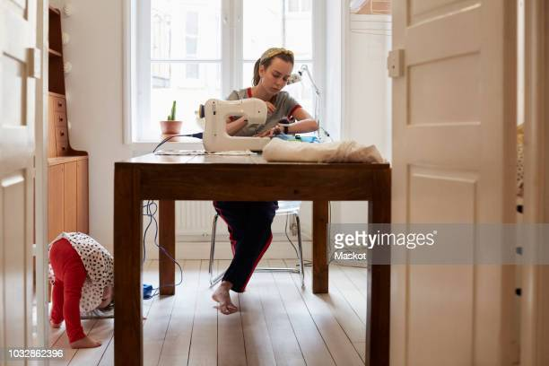 tailor sewing at table while daughter playing on floor seen through doorway at home - 裁縫 ストックフォトと画像