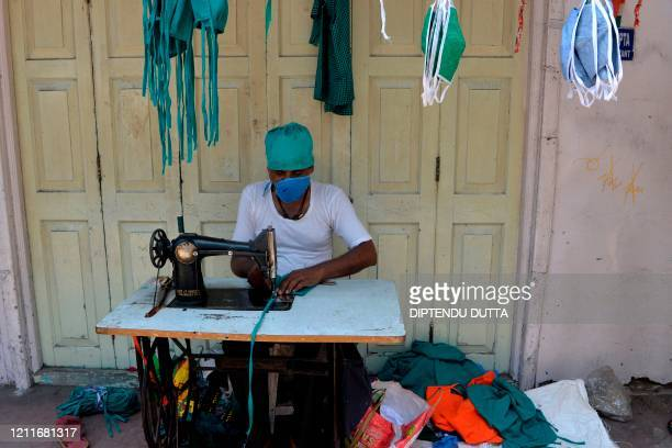 Tailor sews facemasks at a roadside during a nationwide lockdown imposed as a preventive measure against the spread of the COVID-19 coronavirus, in...