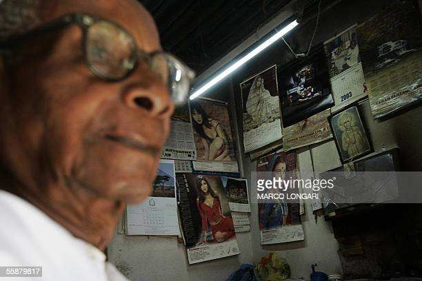 A tailor sits on the doorsteps of his shop whose walls are plastered with Indian Holy images as well as Bollywood stars icons in Stone Town Zanzibar...