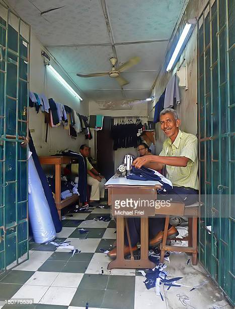 Tailor sitting at his desk with sewing-machine and material smiles out to the street from inside his little shop.