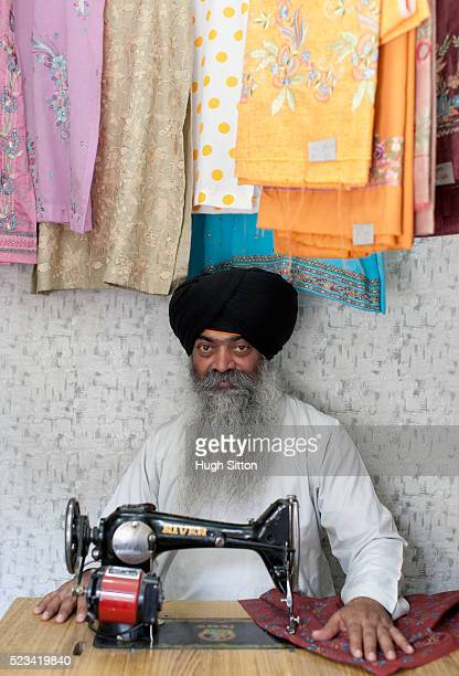 tailor sitting at sewing machine - hugh sitton stock pictures, royalty-free photos & images