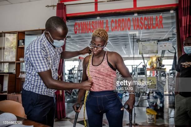 Tailor takes measurements of Kenyan para-rower athlete Asiya Mohammed to make her dress for the Tokyo 2020 Paralympic Games opening ceremony at Tudor...