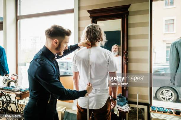tailor taking customers measurements for bespoke suit - custom tailored suit stock pictures, royalty-free photos & images