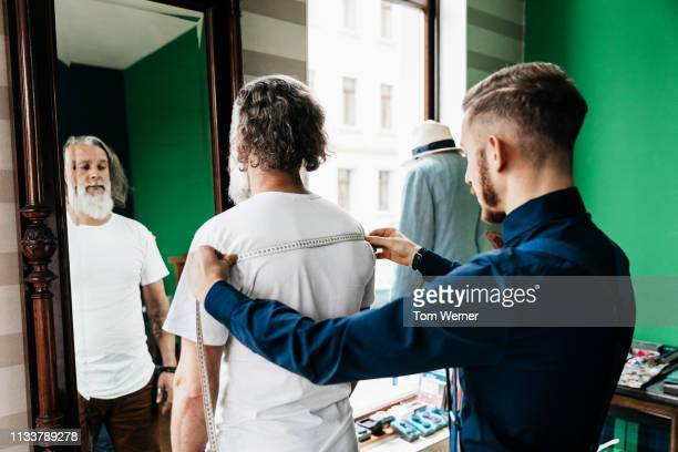 tailor taking customers measurements for suit - custom tailored suit stock pictures, royalty-free photos & images
