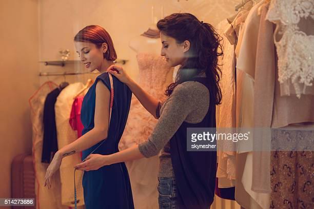 Stellen Sie dem Kunden Maße in Bekleidungsgeschäft.