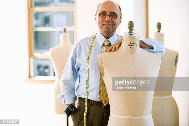 Tailor with arm on dress forms