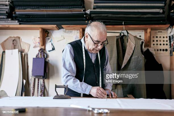 tailor with measuring tape around neck working with material at bench - working seniors stock pictures, royalty-free photos & images