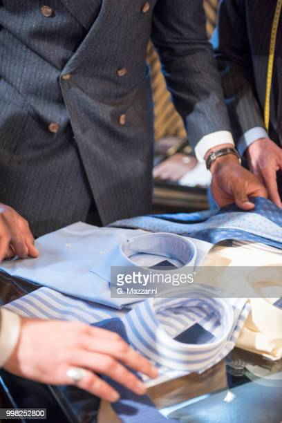 tailors and customer looking at shirts in tailors shop, detail - custom tailored suit stock pictures, royalty-free photos & images