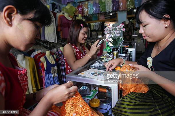 Tailors sew decorations onto dresses in Bogyoke Aung San Market in Yangon Myanmar on Tuesday Oct 14 2014 Myanmars economy is set to grow more than 8%...