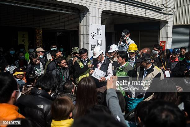 Tainan's Mayor William Lai and Cheng Mingchang president of Tainan civil engineers association brief relatives on the rescue operation of a building...