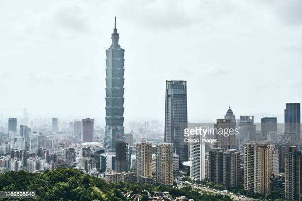 taipei 101 amidst modern buildings against sky in city - taipei stockfoto's en -beelden