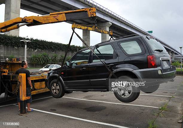Taipei City Government engineering staff tows a vehicle from Riverside Park in New Taipei City on July 12 2013 Hundreds of villagers were evacuated...