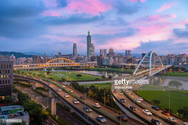 taipei city sunset with road intersection and the taipei101 building at the center of the frame - impossiable stock pictures, royalty-free photos & images
