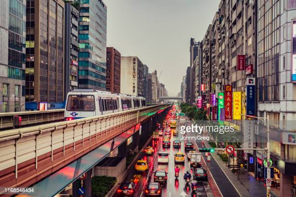 taipei cityscape in rain with monorail train and urban traffic - taipei stock pictures, royalty-free photos & images