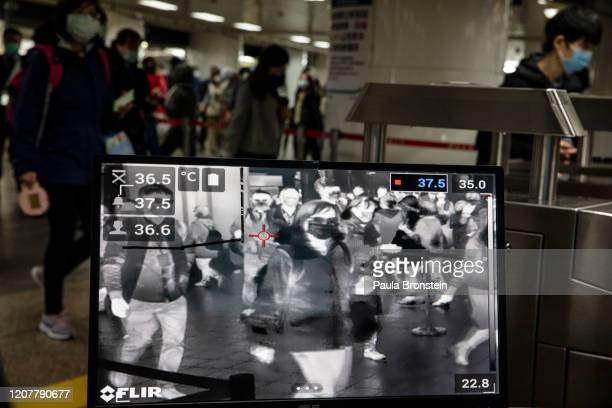 Taipei metro staff in the MRT station monitor the temperatures of passengers with a thermal scanner on March 19 2020 in Taipei Taiwan Taiwan...