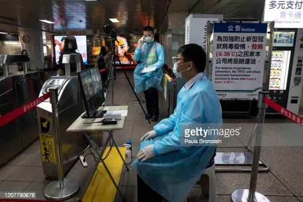 Taipei metro staff in the MRT station monitor the temperatures of passengers with a thermal scanner on March 19, 2020 in Taipei, Taiwan. Taiwan,...