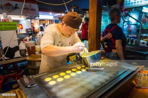 Taipei night market cook making pancakes at street stall Taiwan