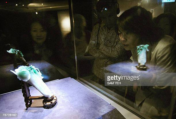 A group of tourists admire a jade cabbage the most popular treasured collection of Taipei's National Palace Museum 28 March 2007 The museum admitted...