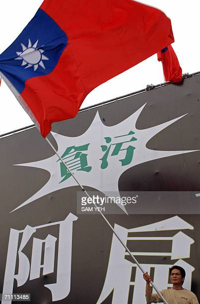A supporter of Taiwan's opposition People First Party waves the national flag in front of a billboard printed with words such as graft and corruption...