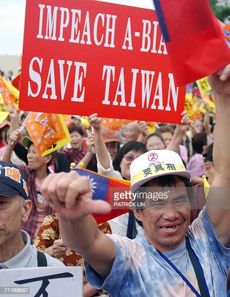 """Supporter of Taiwan's opposition People First Party gives one thumb down against the backdrop of a placard reading """"Impeach Chen Shui-bian, Save..."""