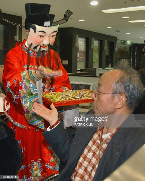 """Taiwanese man wearing a """"god of fortune"""" costume offers candy to an investor at a Taipei securities trading house, 26 February 2007. Taiwan share..."""