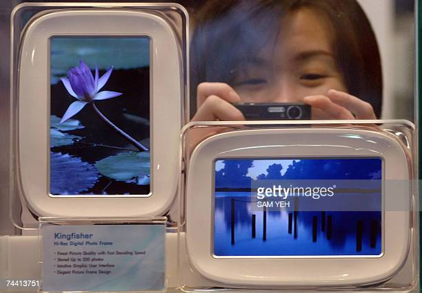 Woman takes a photo of new digital photo frames allowing a user to display pictures taken directly from their camera, during the Taipei International...