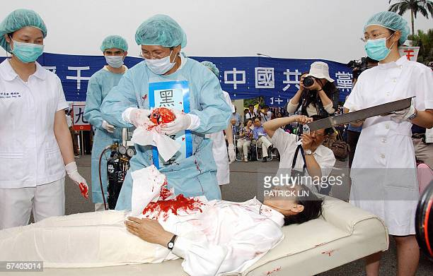 During a rally joined by thousands of Falun Gong practitiioners at Taipei 23 April 2006, four demonstrators play in an action drama against what they...