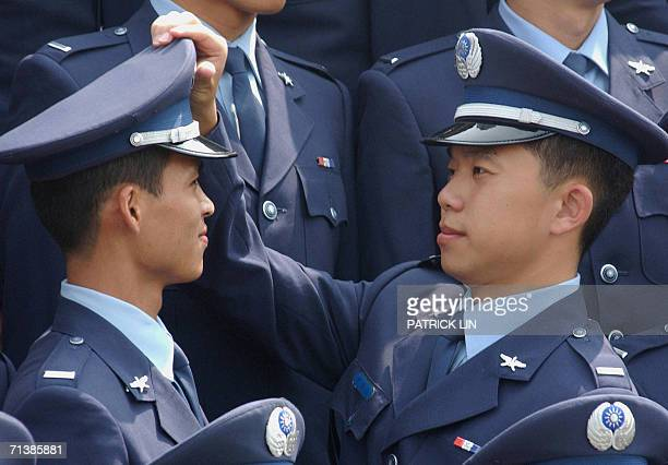Graduates of Taiwan's air force academy adjust their hats during their graduation ceremony in Taipei 07 July 2006 Taiwan's President Chen Shuibian...