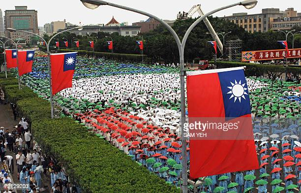 Students wear the umbrella hats as they take part in National Day parade celebrations along a street adorned with Taiwan flags in Taipei 10 October...