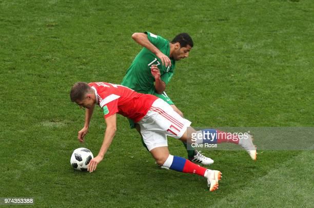 Taiseer Aljassam of Saudi Arabia tackles Roman Zobnin of Russia during the 2018 FIFA World Cup Russia Group A match between Russia and Saudi Arabia...
