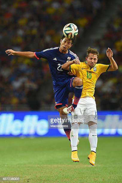 Taishi Taguchi of Japan and Everton Ribeiro of Brazil compete for the ball during the international friendly match between Japan and Brazil at the...
