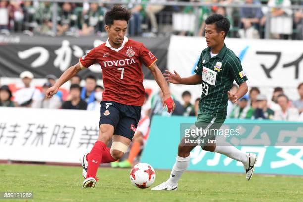 Taishi Taguchi of Nagoya Gampus competes with Yuto Ono of FC Gifu during the JLeague J2 match between FC GIfu and Nagoya Grampus at Nagaragawa...