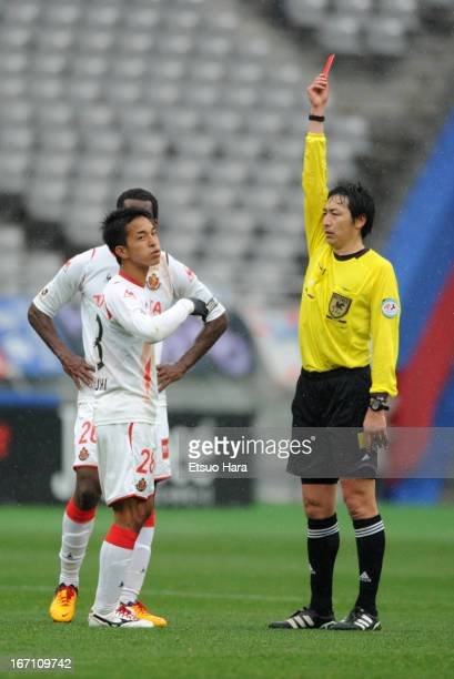Taishi Taguchi of Nagoya Grampus is shown a red card by referee Tomohiro Inoue during the JLeague match between FC Tokyo and Nagoya Grampus at...