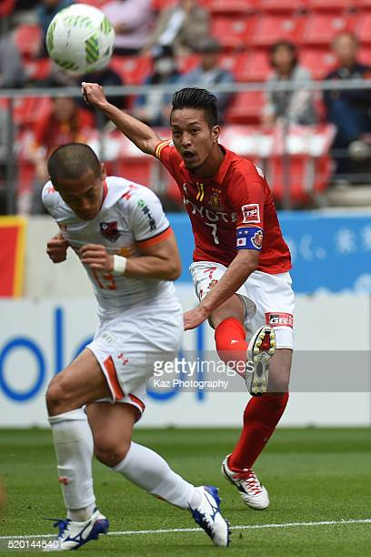 Taishi Taguchi of Nagoya Grampus shoots the ball under the pressure from Ryo Okui of Omiya Ardija during the J.League match between Nagoya Grampus...