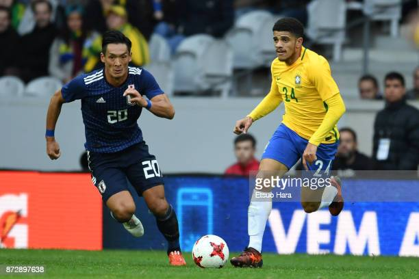 Taison of Brazil and Tomoaki Makino of Japan compete for the ball during the international friendly match between Brazil and Japan at Stade...