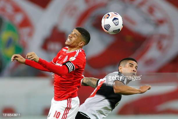 Taison of Internacional jumps for the ball with Jorge Recalde of Olimpia during a match between Internacional and Olimpia as part of Group B of Copa...