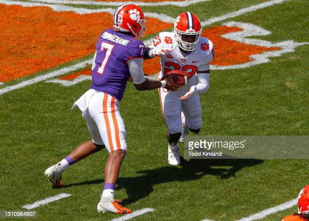 Taisun Phommachanh of the Clemson Tigers hands off to Lyn-J Dixon during the Clemson Orange and White Spring Game at Memorial Stadium on April 3,...