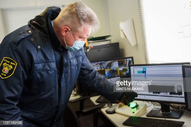 Taivo Hanzens, deputy head of Paternieki custom office shows a scan of a truck on a monitor inside a truck examination building at the Latvian-...