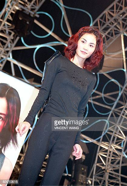 Taiwan EMI star Fay Wong stands covered in sake following the breaking open of a barrell to promote her new album Sing and Play in Tokyo 21 October...