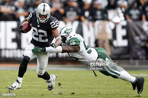 Taiwan Jones of the Oakland Raiders breaks a tackle by Demario Davis of the New York Jets as he runs for a 59yard touchdown during their NFL game at...