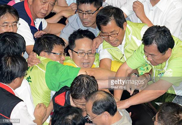 Taiwan legislators scuffle with each other in reaction to a bill due to pass on whether to rebuild the fourth nuclear power plant at parliament in...