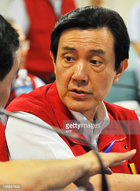 Taiwan President Ma Yingjeou listens during a visit at the Danshuei River Basin flood control command center in the Banqiao District of New Taipei...